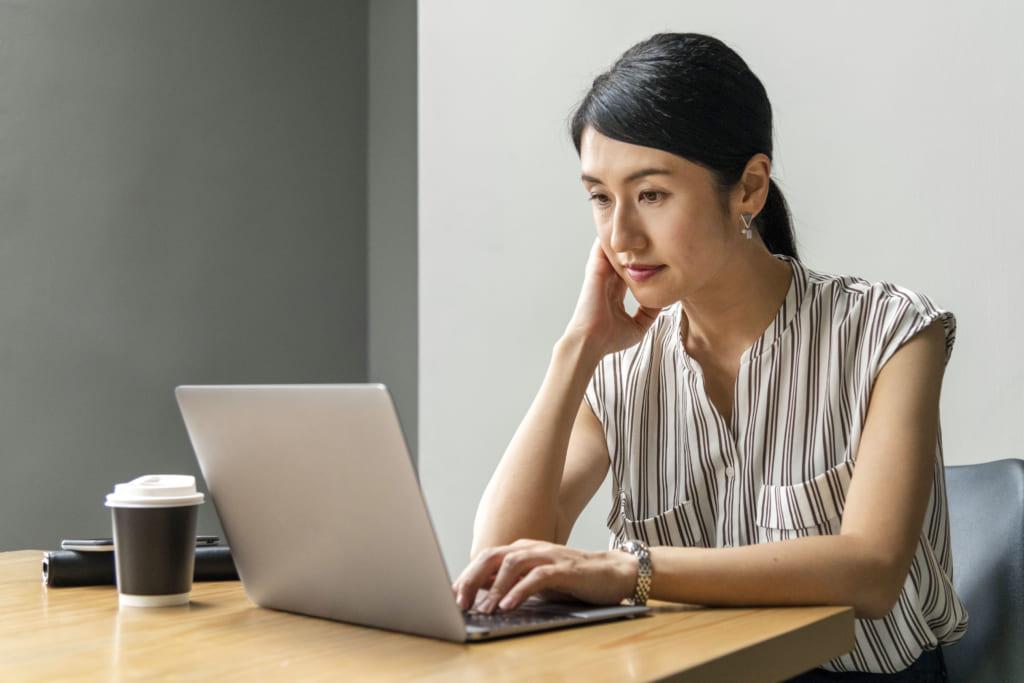 パソコンで文章を読む女性